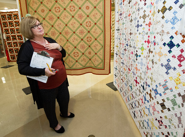 Carol Elmore, of Manhattan, Kan., at the Little Balkans Quilt Quild Show, appraises a quilt made by the late Mary LeClerc, of Pittsburg, who died in July. The quilt is one of 208 entered in this year's contest.<br /> Globe | Laurie Sisk