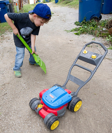 Four-year-old Titus Otero, from College Heights Christian Church, lends a hand in cleaning up an alley between Sergeant and Moffett streets in North Joplin during the Great Day of Service on Sunday. Though too young to operate power tools, Otero helped out with his toy rake and by picking up trash.<br /> Globe | Laurie Sisk