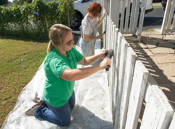 """Volunteer Wrandi Clayton, front, and homeowner Jody Livingston scrape paint in preparation for a fresh coat on Livingston's Carl Junction home on Saturday. About 120 volunteers from Habitat for Humanity's """"Brush with Kindness"""" program and Hearts and Hammers helped beautify 16 sites in Webb City, Carthage, Carl Junction and Joplin on Saturday.<br /> Globe 