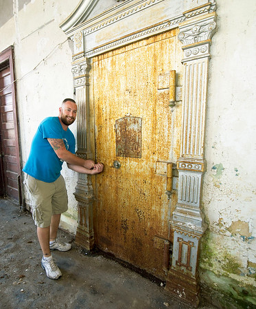 Brock Powell, of Powell's Construction and Flooring, stands near a rusted, metal safe inside the old First National Bank Building in Carterville on Friday. Powell plans to renovate the building into four large apartments, with retail space on the groundfloor.<br /> Globe | Laurie Sisk