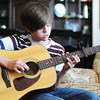 Globe/T. Rob Brown<br /> Grant Landis, 13, who has recorded and co-written several pop songs recently, warms up on an acoustic guitar at his Joplin home.