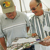 Globe/Roger Nomer<br /> Dennis Johnston, former Treece resident, left, and Bill Blunk, former Treece mayor, look over a recent EPA calendar featuring the city of Treece following Friday's ceremony.