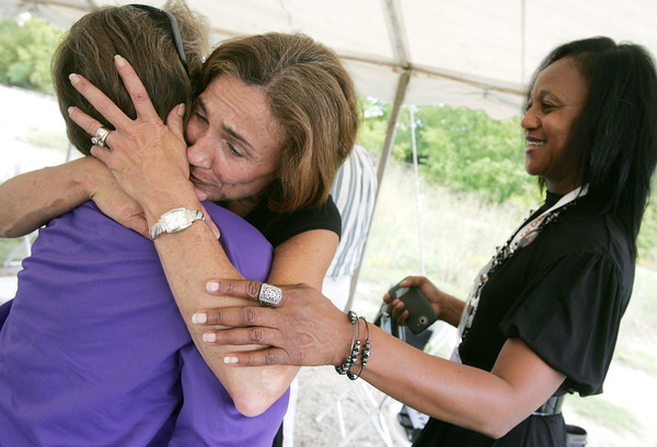 Globe/Roger Nomer<br /> Crystal Gatewood, Cherokee County Clerk, center, gives a hug to Judy Blunk, former Treece councilwoman, as Janetta Coats, Community Involvement Coordinator EPA Region 6, looks on after Thursday's ceremony in Treece, Kan.