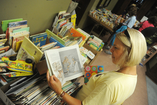 Globe/Roger Nomer<br /> Verna Lou Smith, Pittsburg, browses the selection of children's books at the annual book sale at the Pittsburg Public Library on Saturday morning.