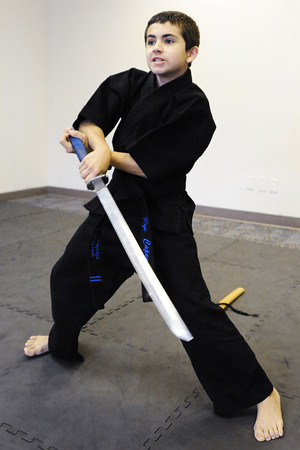 "Globe/T. Rob Brown<br /> Riley ""Rye"" Capen, 12, a second-degree blackbelt in Taekwondo, swings his sword Wednesday, Sept. 26, 2012, at the Team Victory Martial Arts dojo in Joplin."