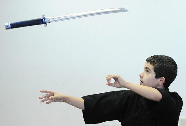 """Globe/T. Rob Brown<br /> Riley """"Rye"""" Capen, left, 12, a second-degree blackbelt in Taekwondo, flips his sword through the air Wednesday, Sept. 26, 2012, at the Team Victory Martial Arts dojo in Joplin."""