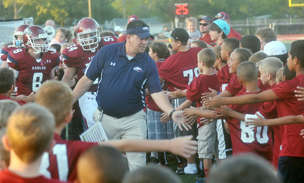 Globe/Roger Nomer<br /> Joplin High Head Coach Chris Shields runs through a tunnel of Joplin Youth Football players before Friday's game at Junge Stadium.  The players and cheerleaders of the youth league were honored at halftime of the game.