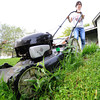 Globe/T. Rob Brown<br /> Cheyenne Neuenschwander, 14, of Carl Junction, mows a lawn near the intersection of 1st Street and Wall Avenue Sunday morning, Sept. 30, 2012, during the Great Day of Service in Joplin.