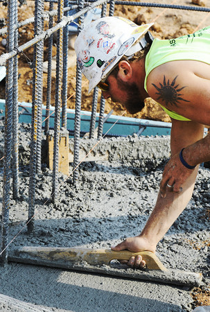 Globe/T. Rob Brown<br /> Tyler Martin, a carpenter/finisher with Branco, smooths concrete footings at the future location of the new Joplin East Middle School in Duquesne as foundation work is underway.