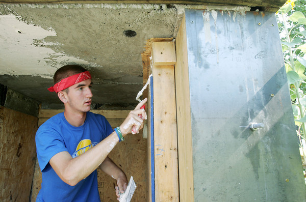Globe/Roger Nomer<br /> Cameron Hein, a volunteer from Pinckney, Mich., helps install a shelter at Dawn Brazelton's house in July.