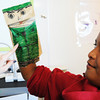 "Globe/T. Rob Brown<br /> Isaiah Kilmete, 12, a sixth-grader, shows his teacher Amanda Mehren his ""goody bag,"" which he made into the puppet of a U.S. soldier, will be sent to soldiers overseas, as part of Patriot Day Tuesday, Sept. 11, 2012, at Joplin East Middle School."
