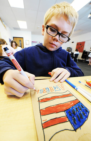 "Globe/T. Rob Brown<br /> A sixth-grader in Amanda Mehren's class writes ""America"" under a U.S. flag he drew on a ""goody bag,"" which will be sent to soldiers overseas, as part of Patriot Day Tuesday, Sept. 11, 2012, at Joplin East Middle School."