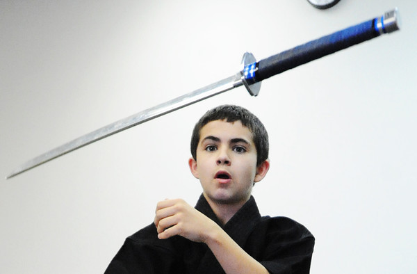 "Globe/T. Rob Brown<br /> Riley ""Rye"" Capen, 12, a second-degree blackbelt in Taekwondo, flips his sword through the air Wednesday, Sept. 26, 2012, at the Team Victory Martial Arts dojo in Joplin."