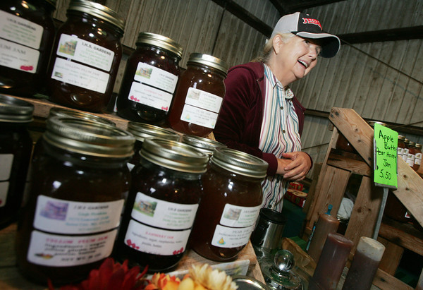 Globe/Roger Nomer<br /> Linda Hawkins, with IHS Gardens in Stotts City, lets visitors sample her fruit butters and jams at Ag Days in Southwest City on Friday.