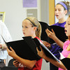 "Globe/T. Rob Brown<br /> Pittsburg (Kan.) Middle School eighth graders Madison Runyun, right, and Olivia Joy, center, and the rest of their class practice a musical piece from Dr. Hubert Bird's ""The Other Side of Storm"" concert-narrative during Virginia Darling's music class Wednesday afternoon, Sept. 26, 2012. Bird is at left in the background."