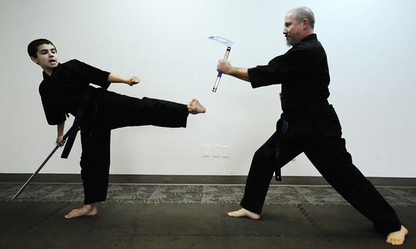 "Globe/T. Rob Brown<br /> Riley ""Rye"" Capen, left, 12, a second-degree blackbelt in Taekwondo, spars with his father, Rex Capen, master instructor, Wednesday, Sept. 26, 2012, at the Team Victory Martial Arts dojo in Joplin."