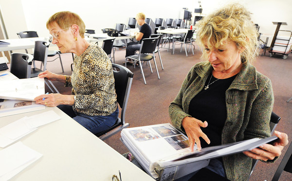 """Globe/T. Rob Brown<br /> Rhonda Cassidy, right, of Topeka, Kan., helps her mother, Jeanene Buchanan, left, now of Webb City, search from lost photos from her former Joplin home Saturday, Sept. 22, 2012, at the Joplin Public Library during a meeting of Operation Photo Rescue and the National Disaster Photo Rescue's """"Lost Photos of Joplin Project."""" Joplin residents whose homes were in the tornado zone searched for their lost photos from the great number that have been collected thus far by the organization. The next meeting will be held from 1-4 p.m. Sept. 29 at SMB Bank in Carthage, near the roundabout."""