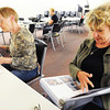 "Globe/T. Rob Brown<br /> Rhonda Cassidy, right, of Topeka, Kan., helps her mother, Jeanene Buchanan, left, now of Webb City, search from lost photos from her former Joplin home Saturday, Sept. 22, 2012, at the Joplin Public Library during a meeting of Operation Photo Rescue and the National Disaster Photo Rescue's ""Lost Photos of Joplin Project."" Joplin residents whose homes were in the tornado zone searched for their lost photos from the great number that have been collected thus far by the organization. The next meeting will be held from 1-4 p.m. Sept. 29 at SMB Bank in Carthage, near the roundabout."