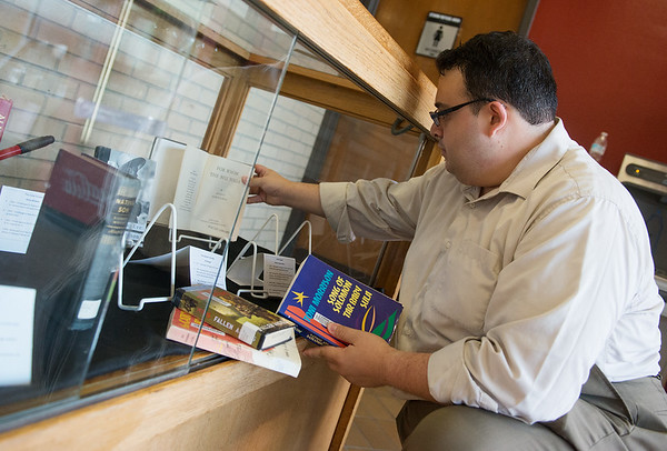 Globe/Roger Nomer<br /> Jorge Leon, learning outreach librarian at Pittsburg State's Axe Library, organizes books in a banned books display on Monday on campus.
