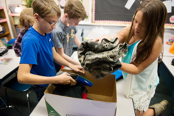 Globe/Roger Nomer<br /> Matthew Lafata, left, Lakin Ballard and Josie Harper, sixth graders at Riverton Middle School, sort clothing for donations to Texas hurrican victims on Thursday at the school.