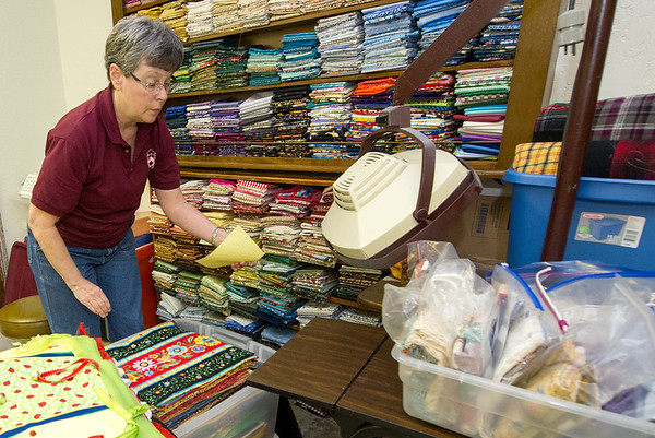 Debbie Dutch Kelley, co-chair of the Community Service Committee for the Joplin Area Town & Country Quilters, gathers placemats in preparation for the Joplin Area Town & Country Quilters 20th Biennial Quilt Show which will be Sept. 22 and 23 at Memorial Hall.<br /> Globe | Laurie Sisk