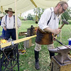 Blacksmith Monty Pugh-Towe, right, fashions a wall hook out of iron as fellow smithy Michael Freund looks on Saturday during Little Balkans Days at the Crawford County Historicl Society. Pictured left is an authentic 1880's lever rivet forge,  Little Balkans Days events continue through Sunday in Pittsburg.<br /> Globe | Laurie Sisk