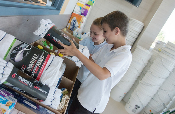 Globe/Roger Nomer<br /> Martin Luther School third graders Skyler Winter and Connor Perry sort cleaning supplies for the Buckets of Hope campaign on Wednesday at the school. The school plans to gather enough donations to send 50 buckets of supplies to hurricane victims in Texas and 50 to Florida, and prepare another 50 to save for future disasters.