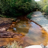 Globe/Roger Nomer<br /> On the south side of East 40 Road in Douthat, Tar Creek is orange from mining waste.