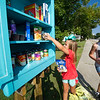 From the left: Sisters Jacee Divine, 7 and Jenna Schulz, 10 restock items in the Blessing Box the family built at their Carterville home. The box is dedicated to the memory of their grandmother, Kathy Divine and was made from one of her old dressers.<br /> Globe | Laurie Sisk