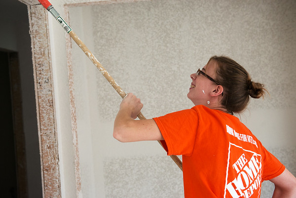 Globe/Roger Nomer<br /> Amy White, head cashier at Joplin Home Depot, paints while working with Habitat for Humanity on Monday.
