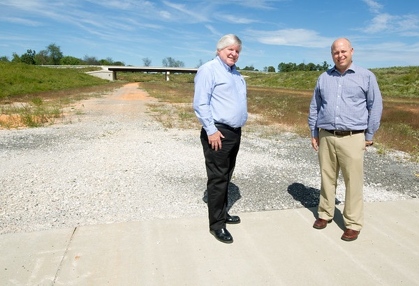 From the left: Jeff Hawkins, executive director of the Northwest Arkansas Regional Planning Commission and Tim Conklin, transportation program manager for NWARPC, stand Thursday at pavements end in Bentonville near County Road 34, where a continuation of the I-49 Bypass project into Missouri is planned.<br /> Globe | Laurie Sisk