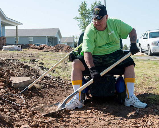 Globe/Roger Nomer<br /> Ron King works on the sidewalk in front of his house on Monday morning.