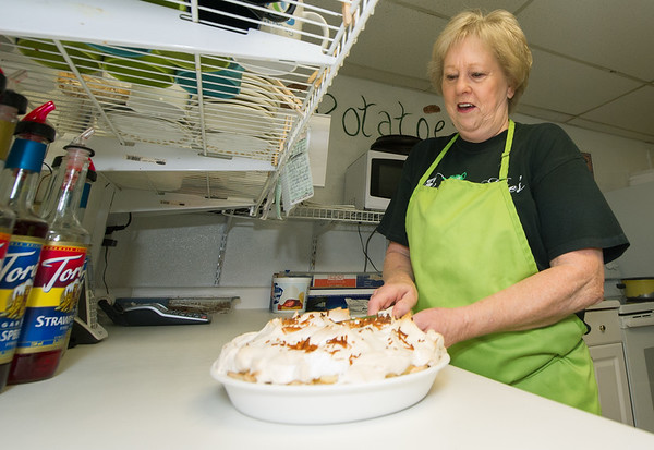 Maggie Mae's Tea Room owner Marsha Hill slices a cocunut cream pie in the kitchen of her business in Miller.<br /> Globe   Laurie Sisk