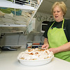 Maggie Mae's Tea Room owner Marsha Hill slices a cocunut cream pie in the kitchen of her business in Miller.<br /> Globe | Laurie Sisk