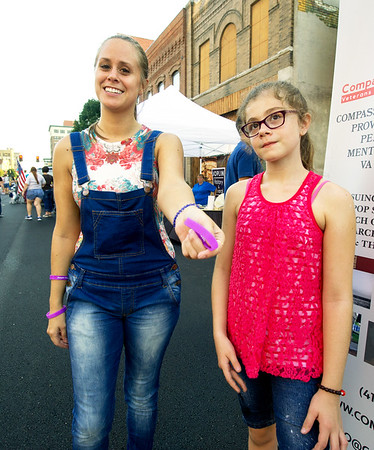 Danita Tamilio displays the recovery awareness bracelets she and other recovering addicts handed out at Third Thursday. Tamilio has been clean and sober two-years while battling an opiate addiction. Also pictured is Tamilio's daughter, Kaylee Carter, 9.<br /> Globe | Laurie Sisk