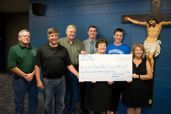 Globe/Roger Nomer<br /> (from left) Greg Emory, Ken Bartholomew, David Drake, and Scott Lone present a check from the Jeff Slama Memorial fund for scholarships to Joplin Area Catholic Schools including Ann Hamlet, St. Mary's Elementary principal, Georgiana McGriff, director of Joplin Area Catholic School System, and Tracey Welch, McAuley and St. Peter's principal, on Thursday at McAuley High School. The main fundraiser for the Jeff Slama Memorial Fund is their annual Chili Cookoff, which takes place on Saturday, Sept. 30, at McAuley High School starting at 5:30 p.m.