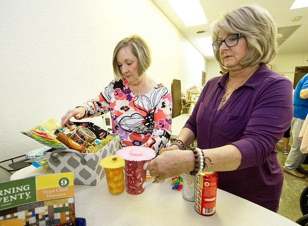 From the left: Kathy Knapp and Terry Brown assemble baskets as fundraisers for the Joplin Area Town & Country Quilters 20th Biennial Quilt Show which will be Sept. 22 and 23 at Memorial Hall.<br /> Globe | Laurie Sisk