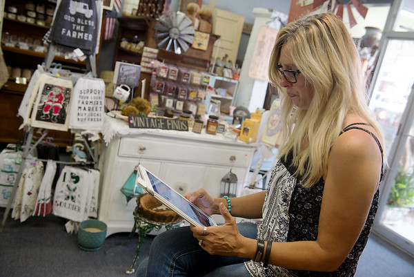 Globe/Roger Nomer<br /> Kathie England-Hinds tearfullly reads an account of addiction online on Tuesday at her store in downtown Joplin. England-Hinds said she has found support in online blogs and groups.