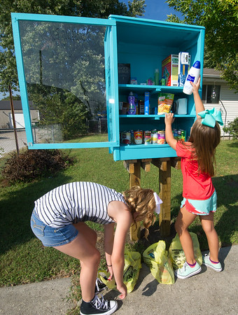 From the left: Sisters Jenna Schulz, 10 and Jacee Divine, 7 restock items in the Blessing Box the family built at their Carterville home. The box is dedicated to the memory of their grandmother, Kathie Divine and was made from one of her old dressers.<br /> Globe | Laurie Sisk