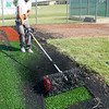 JT Murphy, of Sprinturf, spreads rubber pellets on the new infield at Wendell Redden Field on Friday.<br /> Globe | Laurie Sisk