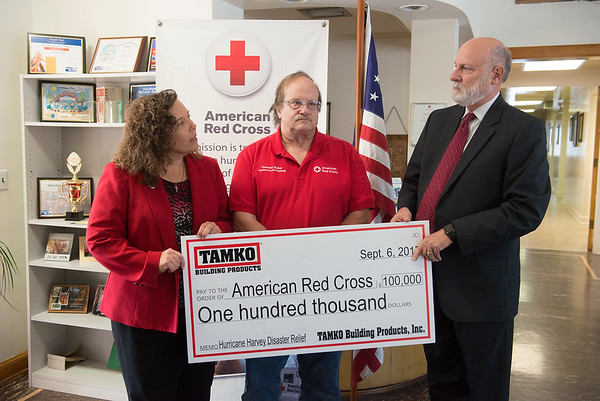 Globe/Roger Nomer<br /> Bob Bradley, vice president and general counsel with TAMKO Building products, right, presents a check to Stacy Burks, executive director for the American Red Cross of Southern Missouri, for Hurricane Harvey disaster relief on Wednesday at the Joplin Red Cross. Also present was long-time Red Cross volunteer Thomas Zeller.