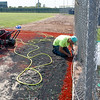 A worker from Sprinturf fastens the edges of the new infield at Wendell Redden Field on Friday.<br /> Globe | Laurie Sisk