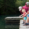 Brenda and Gary Dovin, Green Forest, Ark., help their granddaughter Olivia Headrick, 2, feed fishes at the Roaring River fish hatchery on Friday.<br /> Globe   Roger Nomer