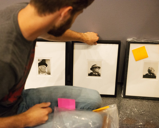 Patrick Laird, a Missouri Southern senior from Perry, Kan., sets up a gallery of photos by Edvard Munch at the Spiva Gallery at MSSU on Wednesday.<br /> Globe | Roger Nomer