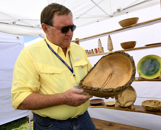 Craftsman Mike Ilkiw, of Bowls for Breasts, discusses the wood turning involve in the creation of this unique bowl during the Joplin Arts Fest on Saturday at Mercy Park. Ilkiw donates a generous portion of his proceeds to the Breast Cancer Foundation of the Ozarks. Ilkiw, of Springfield, lost his first wife to breast cancer in 2011.<br /> Globe   Laurie Sisk