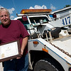 Ron Riediger displays the plaque he was awarded after rescueing a trapped person with his tow truck earlier this year.<br /> Globe | Roger Nomer