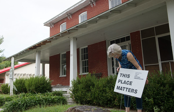 Betsy Flanigan, vice president of the Carthage Historic Preservation Society, straightens a sign at the Sweet House on Thursday.<br /> Globe | Roger Nomer