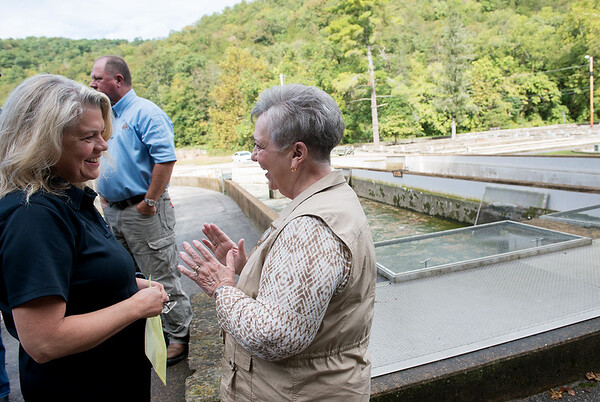 Sara Parker Pauley, director of the Missouri Department of Conservation, left, talks with Carmen Rogers, concessionary at Roaring River, before Friday's groundbreaking at the hatchery.<br /> Globe | Roger Nomer