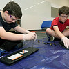 From the left: Siblings Samuel Noran, 11 and Benjamin Noran, 13, investigate the inner components of a keyboard and a laptop during an electronics workshop on Saturday at the Joplin Public Library.<br /> Globe | Laurie Sisk