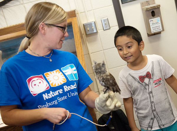 Katie McMurry, a Pittsburg State grad student from Pittsburg, holds a screech owl for Suhasmukul Santra, 6, at PSU's Nature Reach on Tuesday.<br /> Globe | Roger Nomer